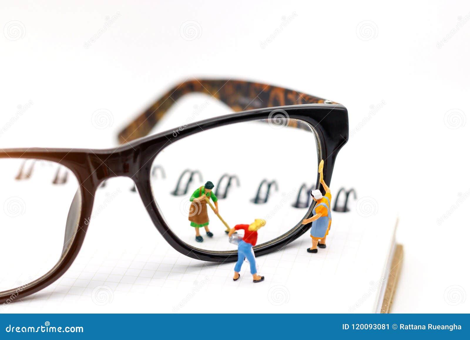 Miniaturowi ludzie pracownika cleaning przyglądają się szkła na książce Jasny Vis