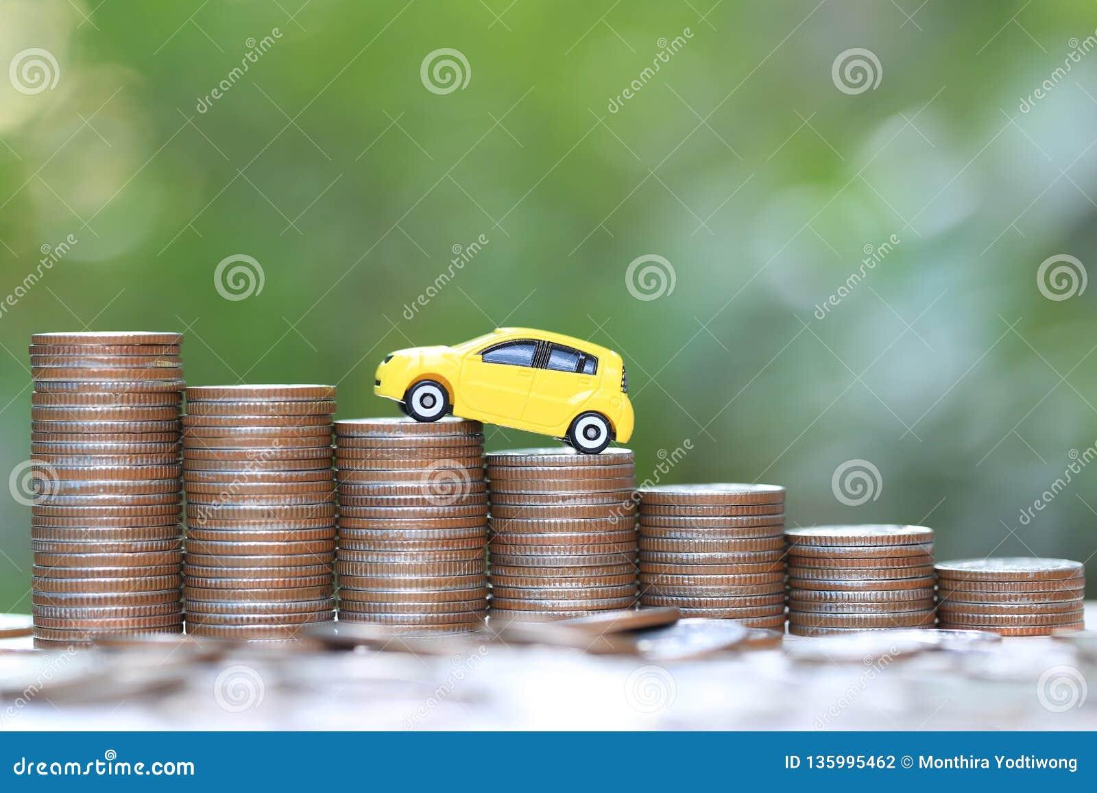 Miniaturowy żółty samochodu model na dorośnięcie stercie moneta pieniądze na natury zieleni tle, oszczędzanie pieniądze dla samoc