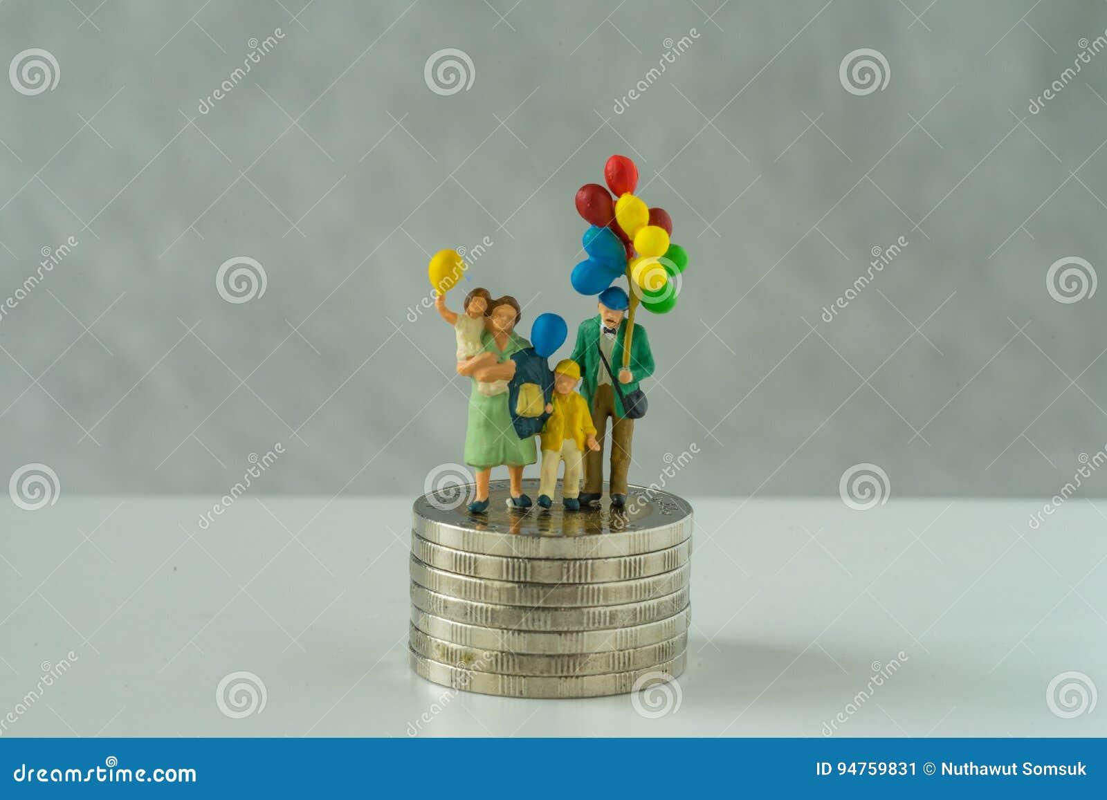 Miniatuurmensen, de ballon van de familieholding zich op stapel muntstukken als financiële zaken bevinden of gelukkig pensionerin