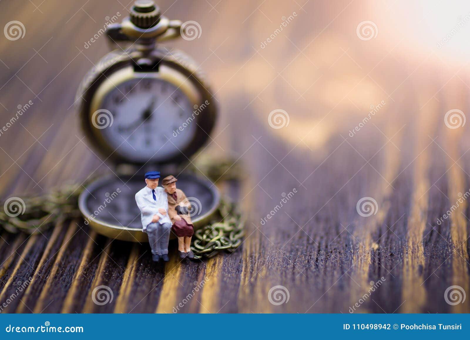 Miniatuurmensen: De oude paren zitten op de klok Beeldgebruik voor samen het doorbrengen van kostbare notulen elke minuut