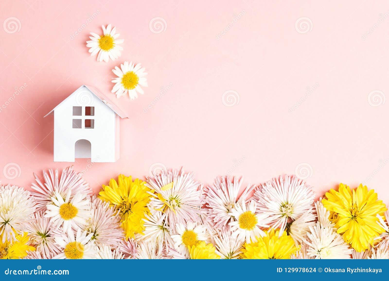 Miniatuurstuk speelgoed huis met bloemen en exemplaarspase op roze backgrou