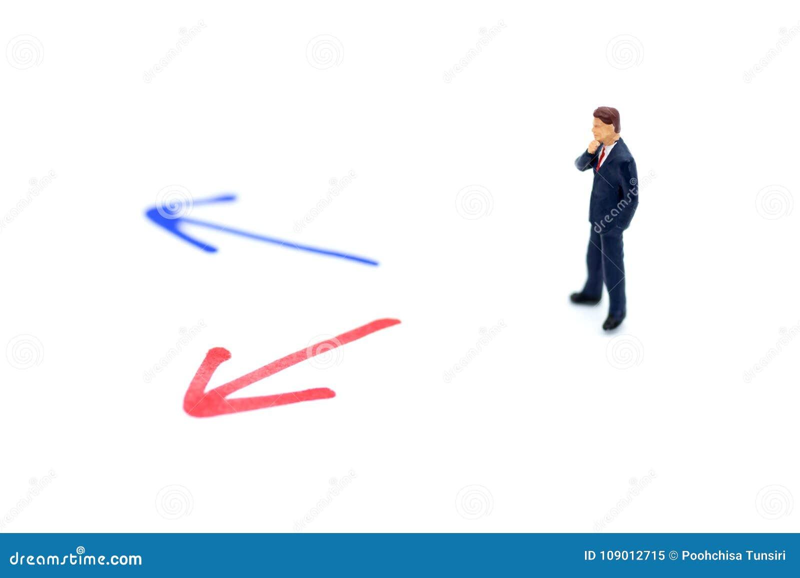Miniatyrfolk: Affärsman som framme står av pilbanaval Avbilda bruk för begrepp för affärsbeslut som är nytt vägen