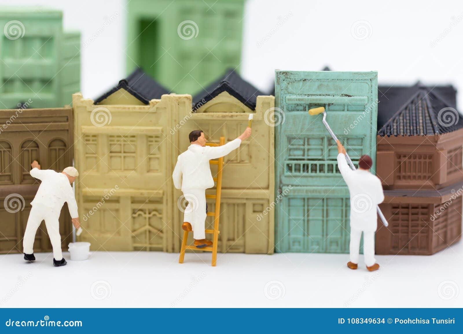 Miniatyrfolk: Arbetare målar byggnaden i stad Bildbruk för affärsidé