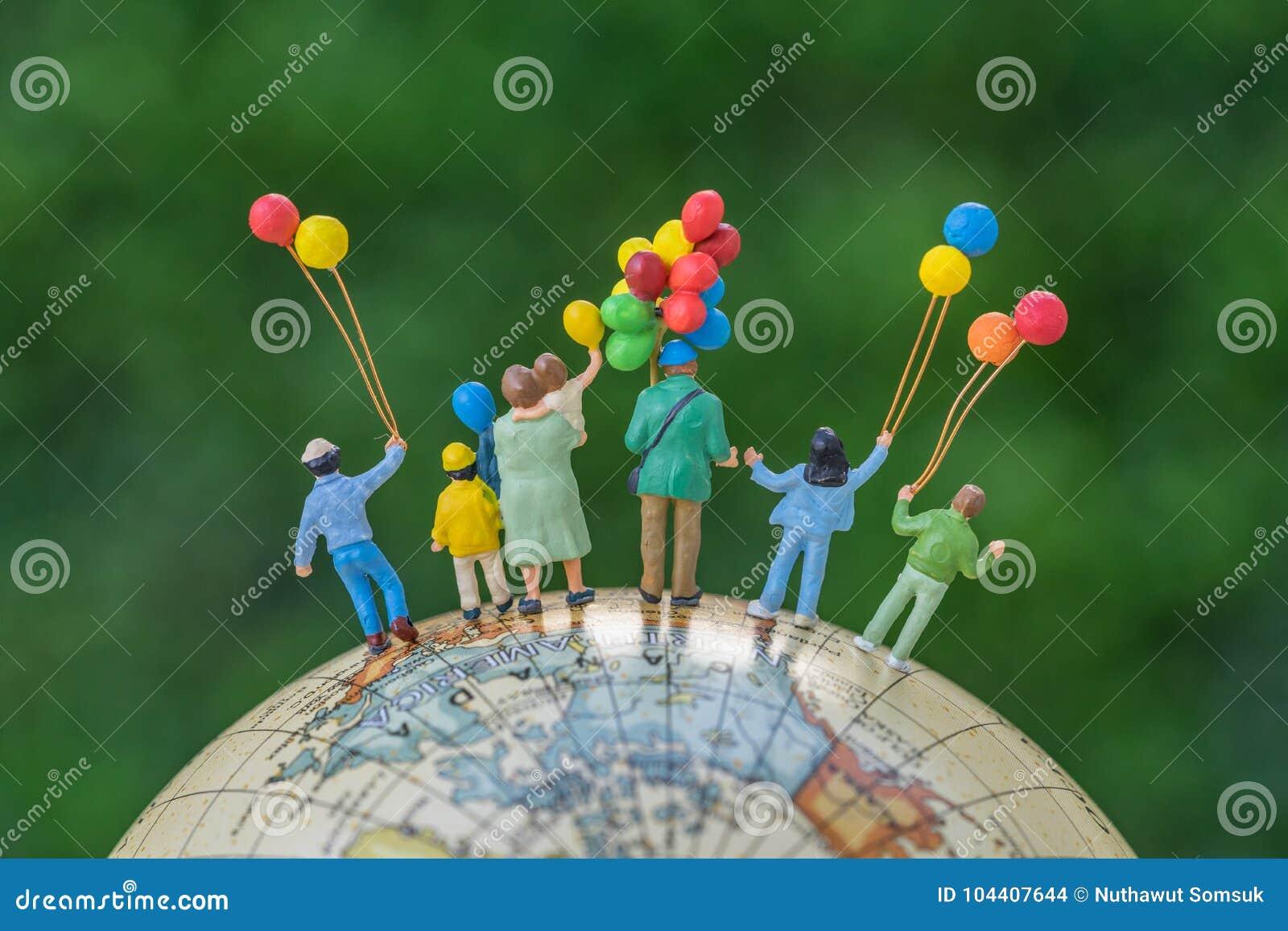 Miniatyrfolkdiagram tillbaka sikt av den hållande ballooen för lycklig familj