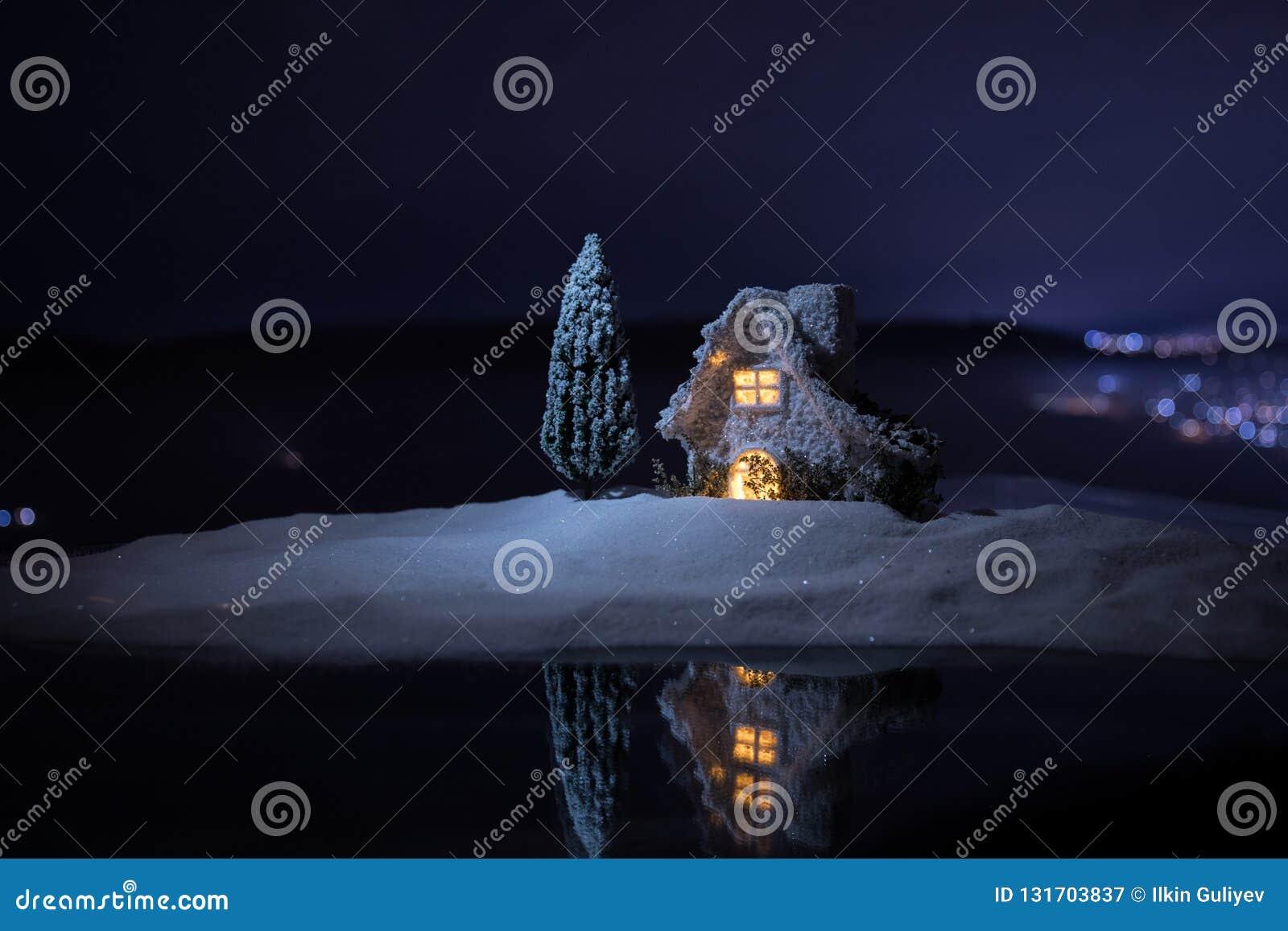 Miniatyrhus för jul och för nytt år i snön på natten med granträdet Litet leksakhus på snö med träd- och bokehstaden