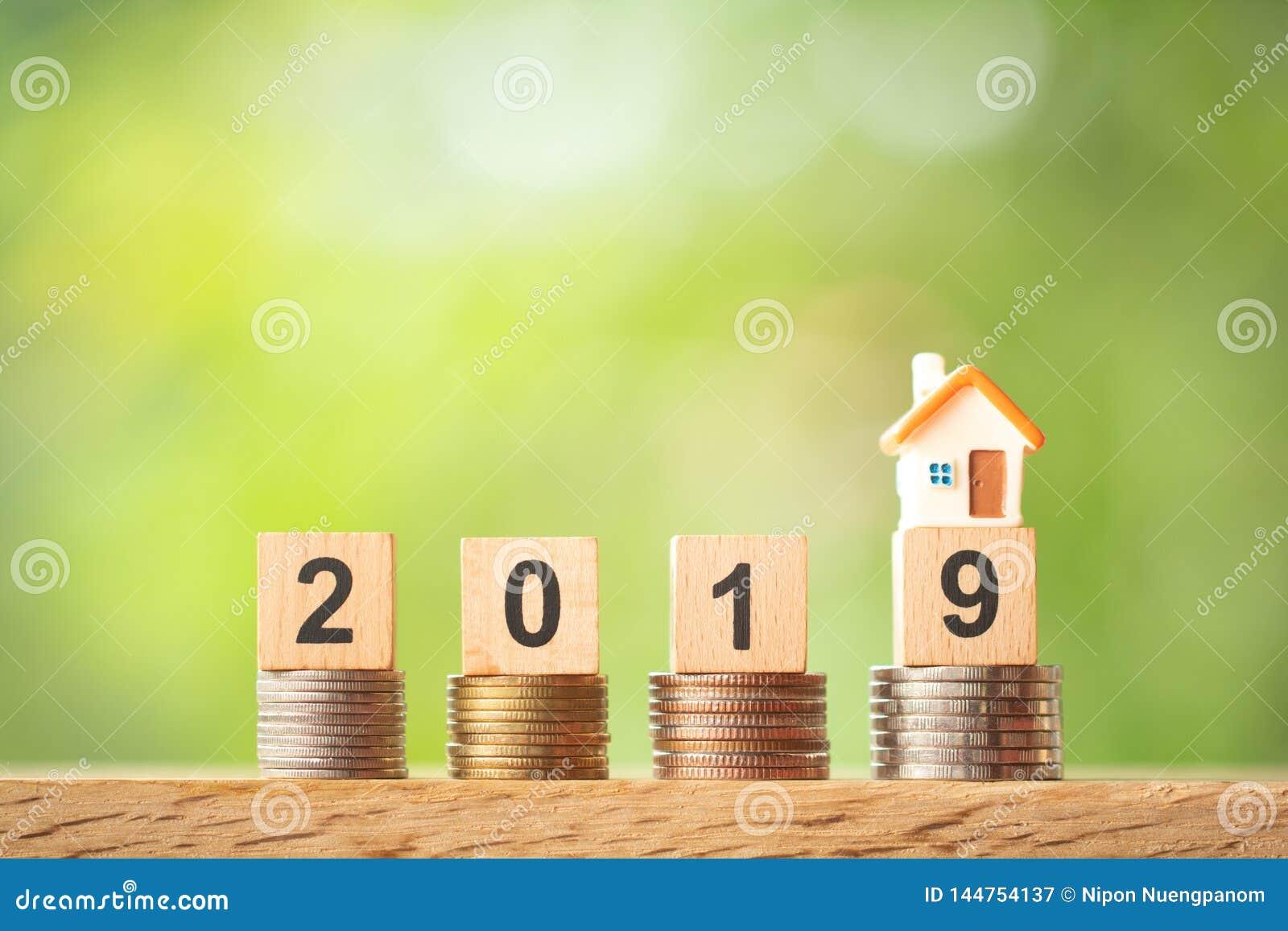 Miniatyrhusmodell på året 2019 på myntbuntar på suddig bakgrund för grönska