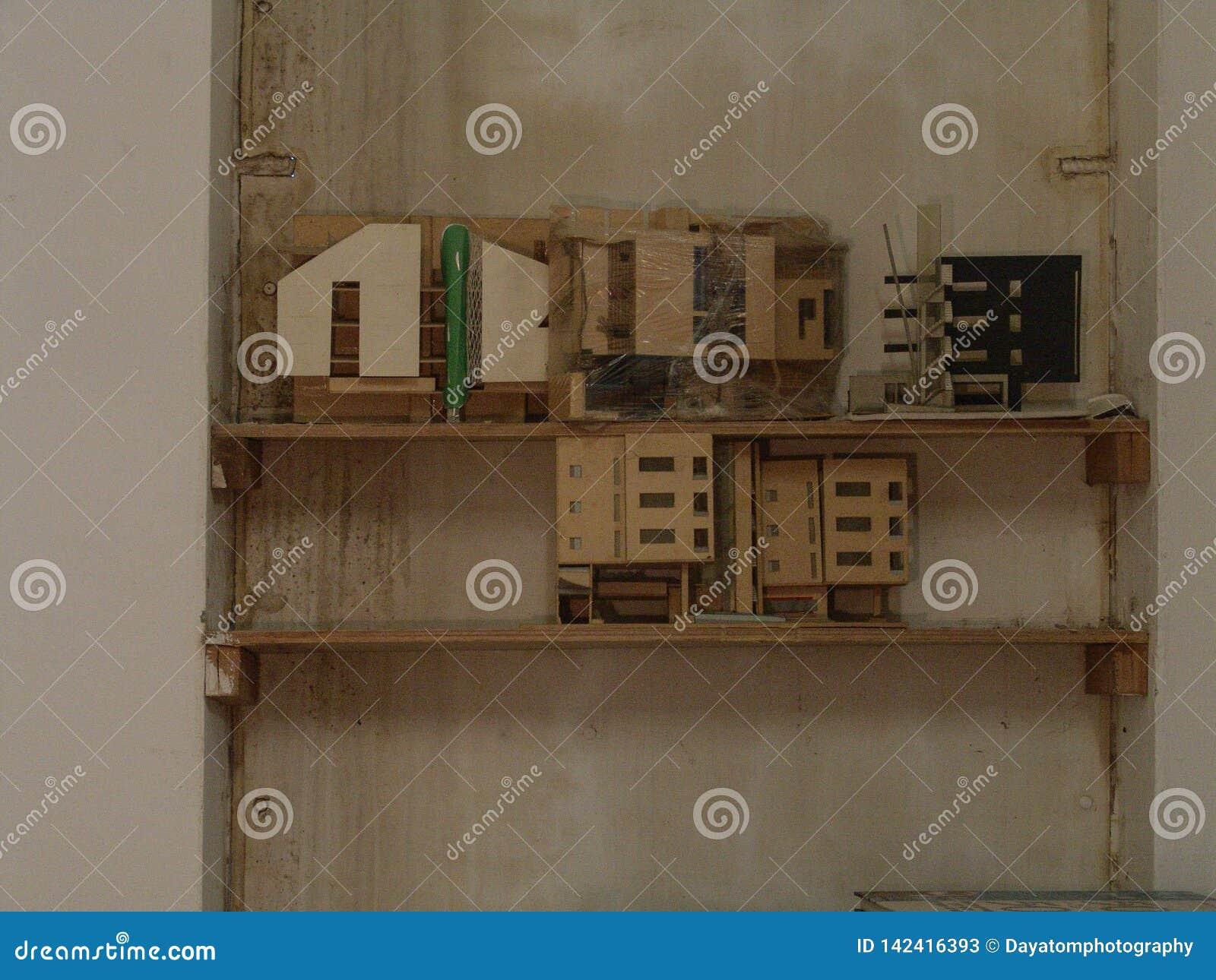 Miniatyrträbyggnader på skärm på en trähylla mot en vägg