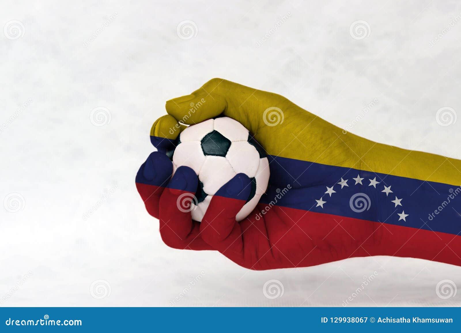 Minibal van voetbal in de geschilderde hand van Venezuela vlag op witte achtergrond