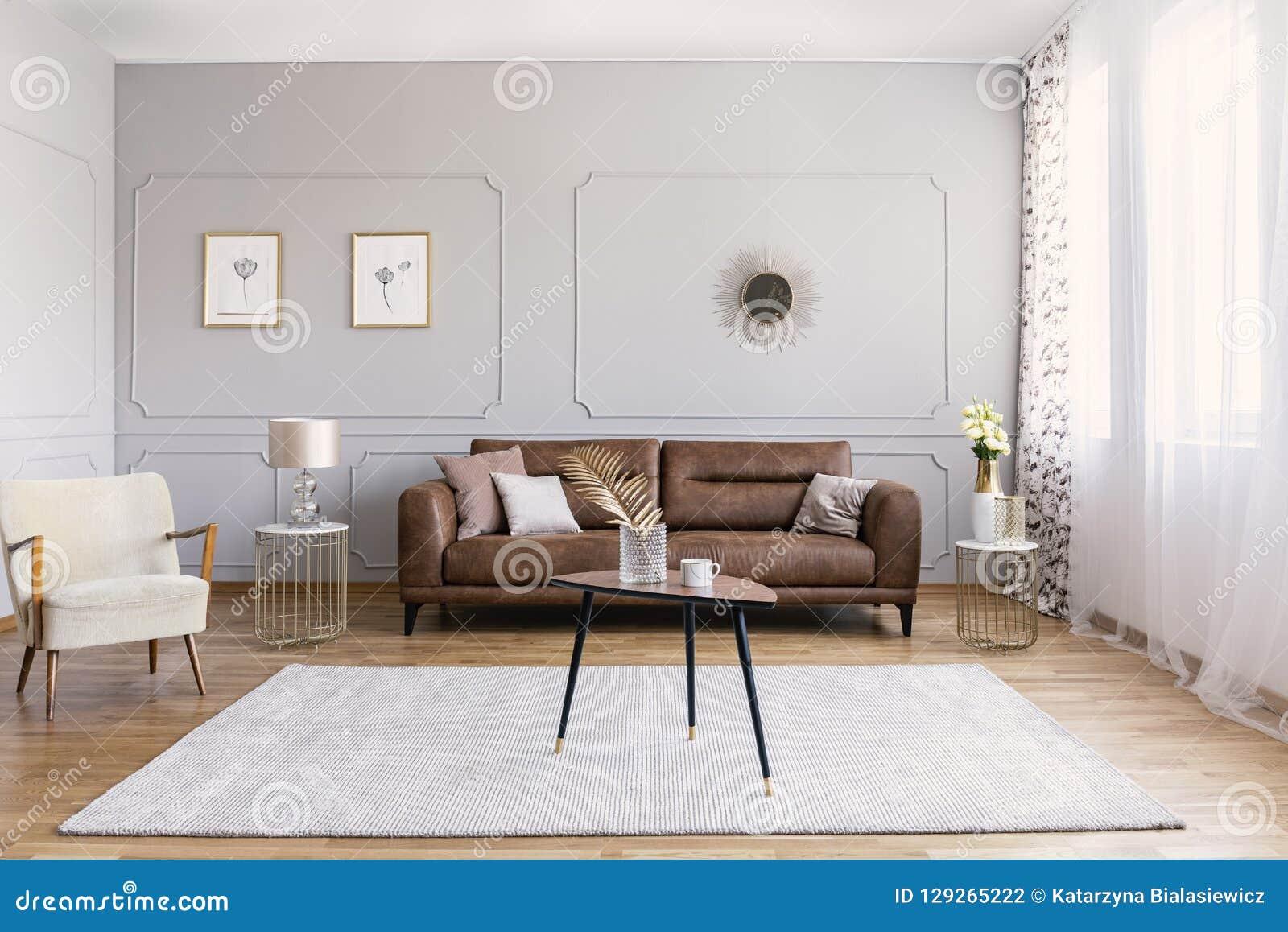 Minimaal binnenlands ontwerp van woonkamer met bruine leerlaag, retro leunstoelkoffietafel en gouden decoratie