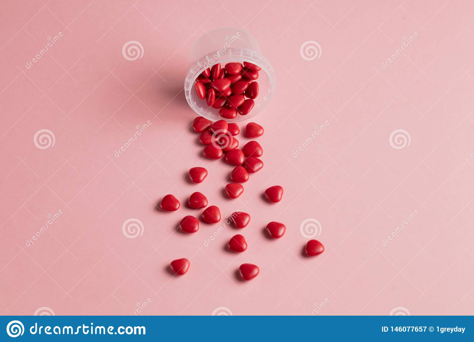Minimal concept . red little hearts with open glass bottle on pink background