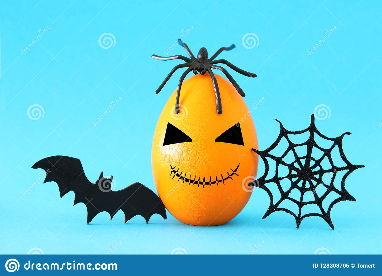 minimal and funny halloween holiday concept. orange egg with scary