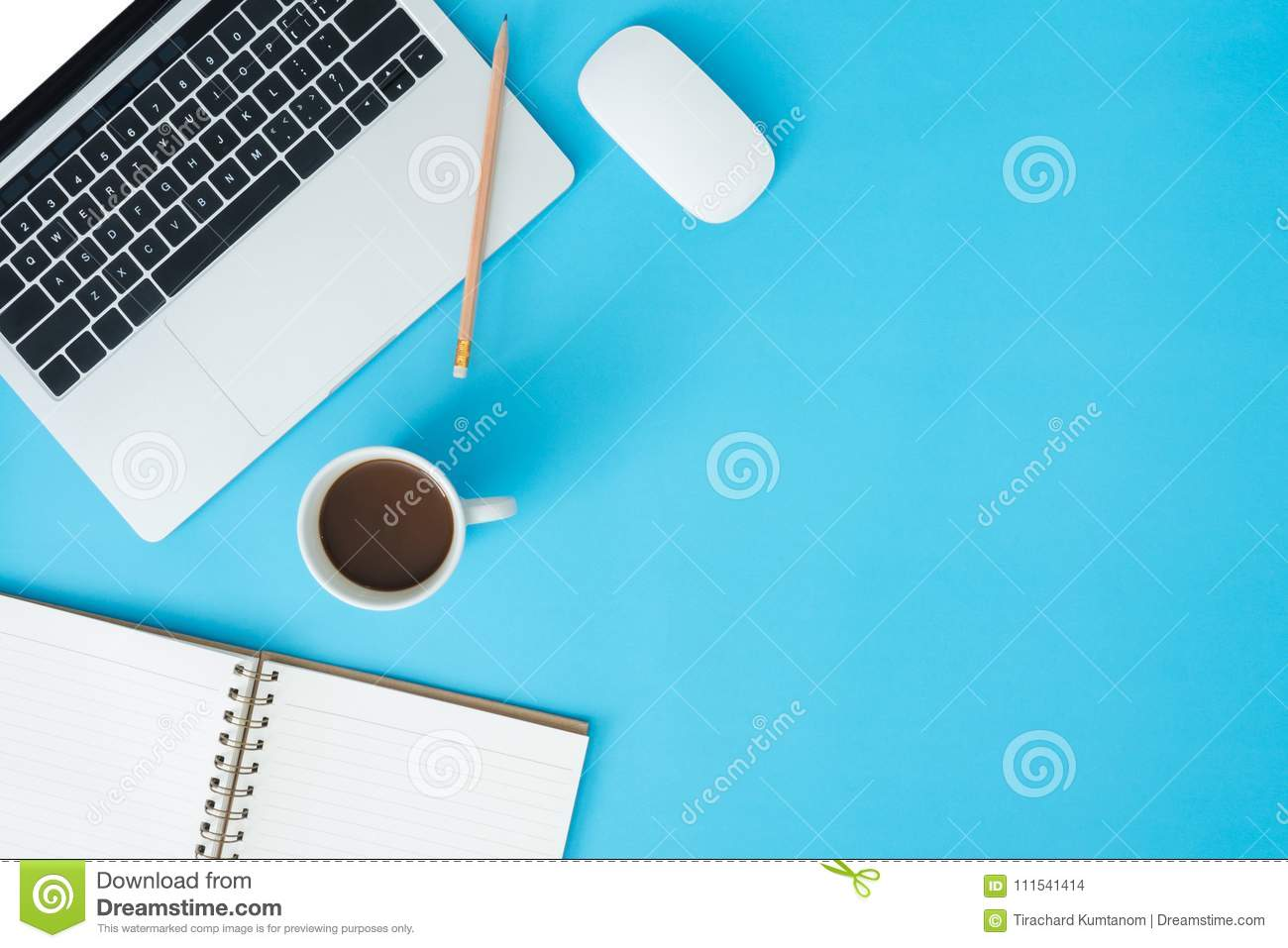 Top view office desk with laptop, notebooks and coffee cup on blue color background. Top view with copy space, flat lay photograph
