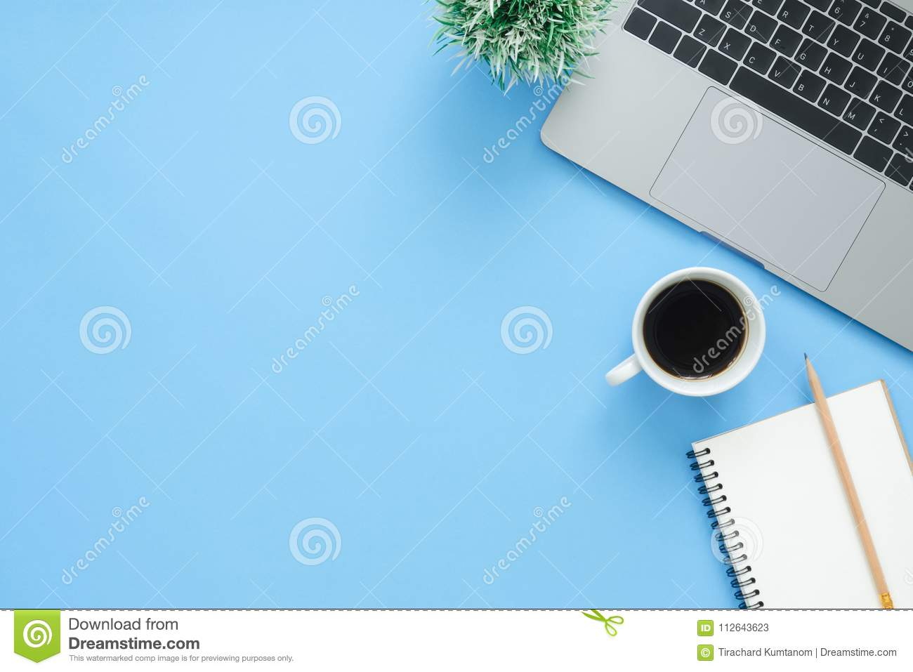 Top view office desk with laptop, notebooks and coffee cup on blue color background.