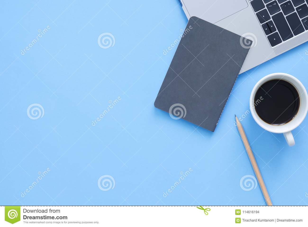 Creative flat lay photo of workspace desk. Top view office desk with laptop, notebooks and coffee cup on blue color background.