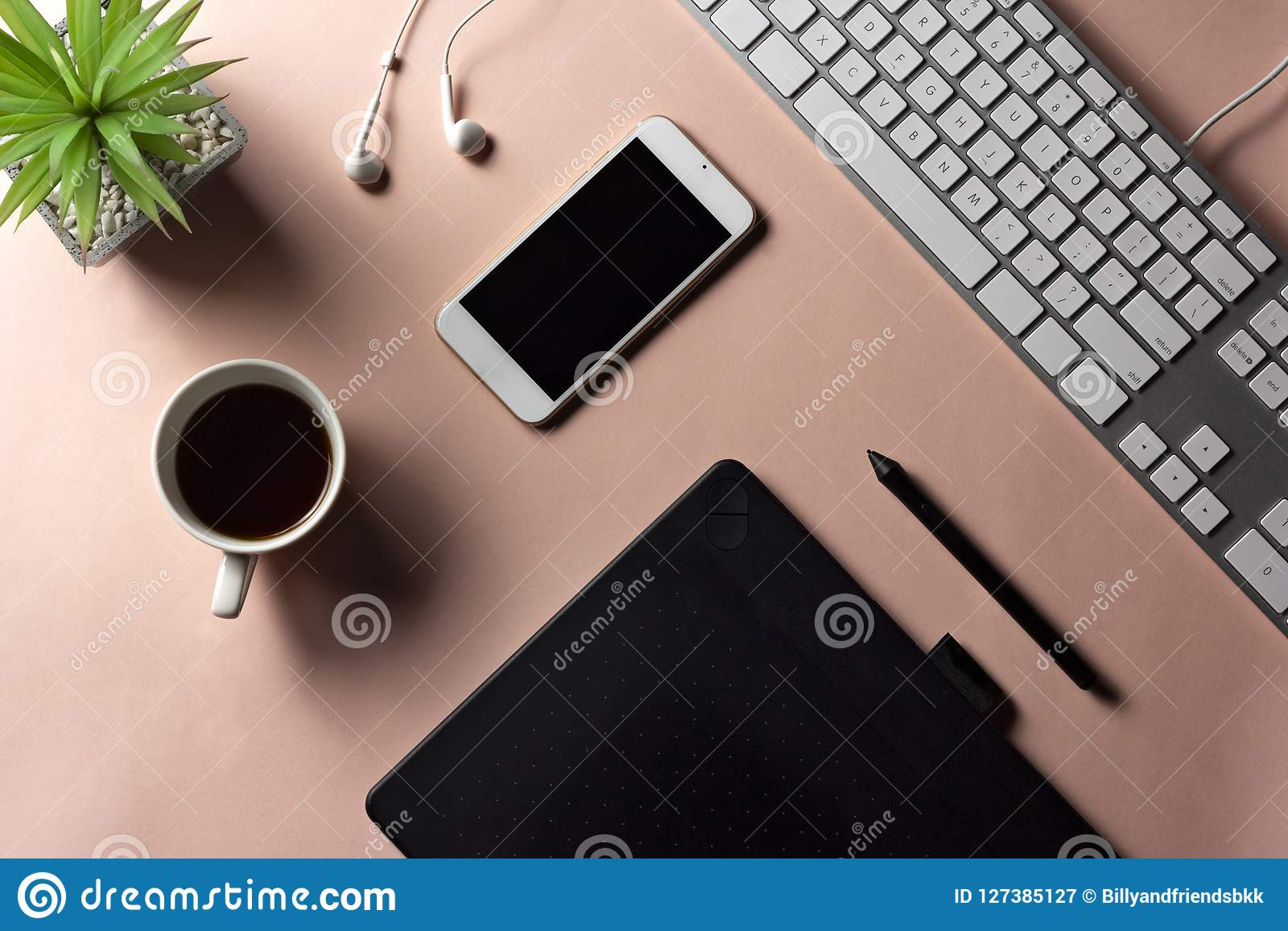 Minimal workspace for designer with electronic goods and espresso coffee on pastel pink background