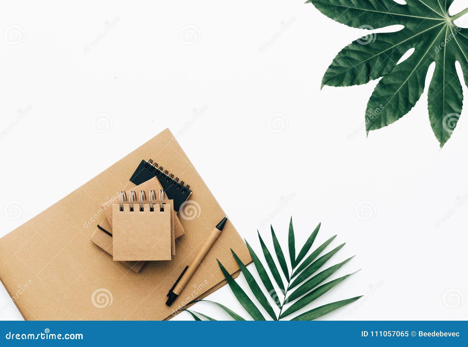 Minimale Schreibtischtabelle mit Briefpapiersatz, -versorgungen und -palmblättern