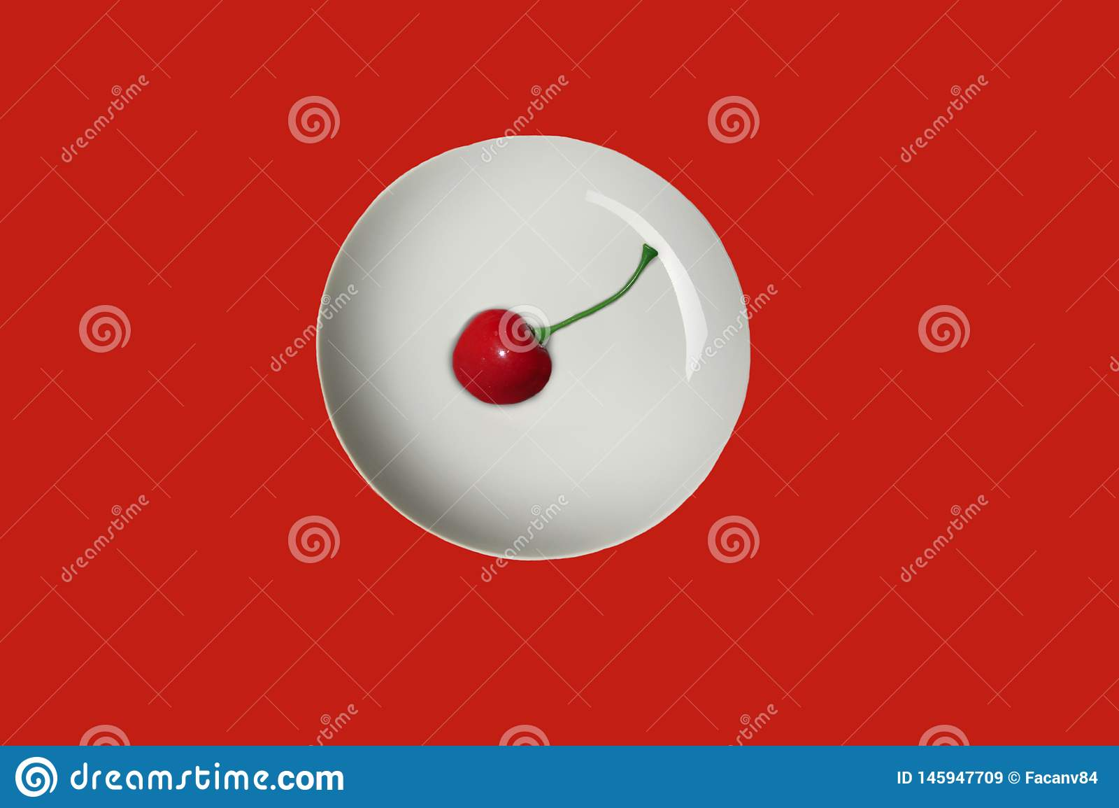 Minimalism in the photo. One ripe, fresh, juicy and tasty cherry in a white plate. Red surface.