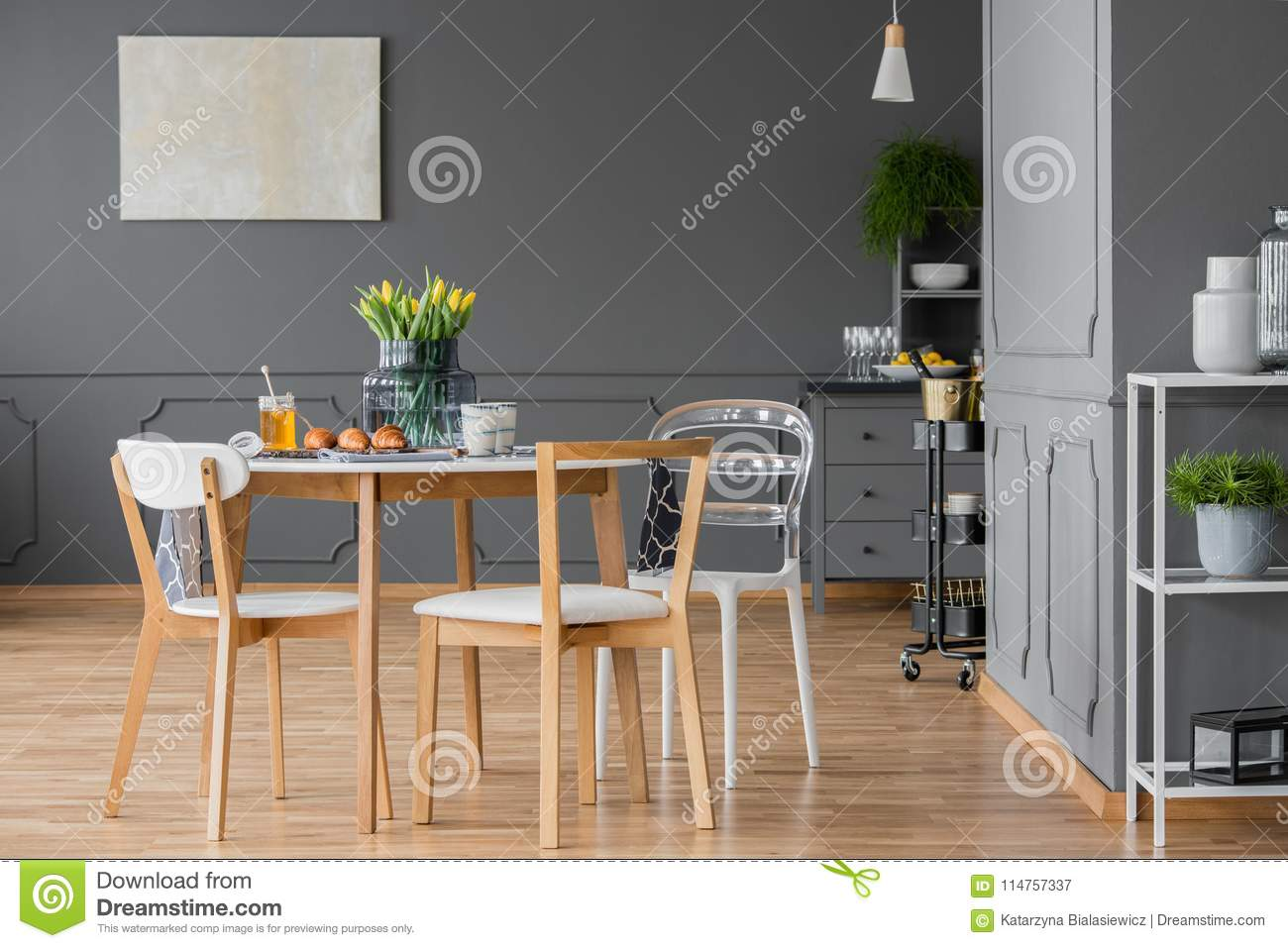 Minimalist wooden set of dining furniture in the middle of a designer open space loft interior with simple decor and elegant dark gray walls