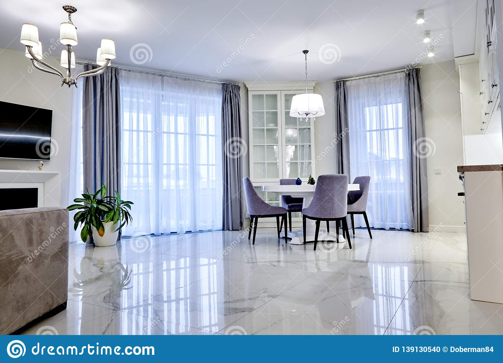 Minimalistic Interior Of Living Room In Light Tone With Marble Flooring Large Windows And A Table For Four Persons Stock Photo Image Of Marble Mansion 139130540