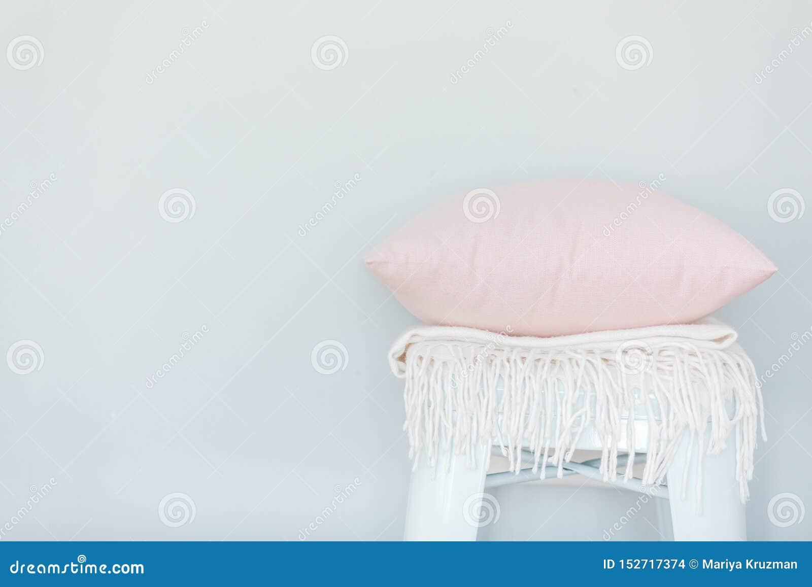 Minimalistic skandinavian beeld van een lichtrose hoofdkussen en een witte plaid op de stoel dichtbij een lichtblauwe muur