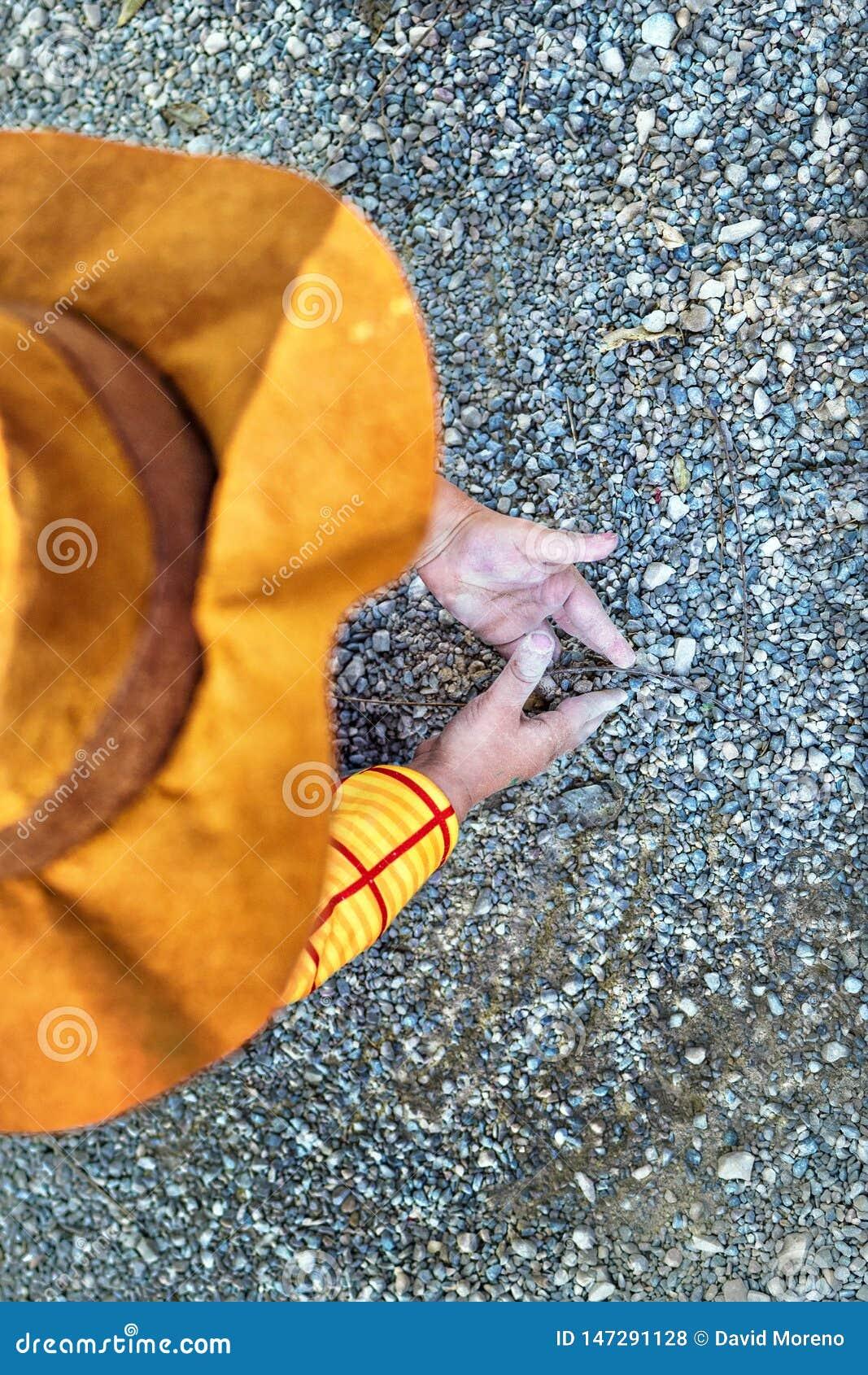 Minimalistische lage hoekmening van jong geitje het spelen met zand Het concept van de kinderjarencreativiteit