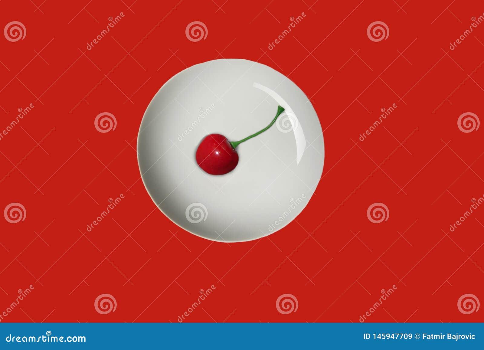 Minimalizm w fotografii Jeden dojrza?a, ?wie?a, soczysta i smakowita wi?nia w bia?ym talerzu, czerwieni powierzchnia