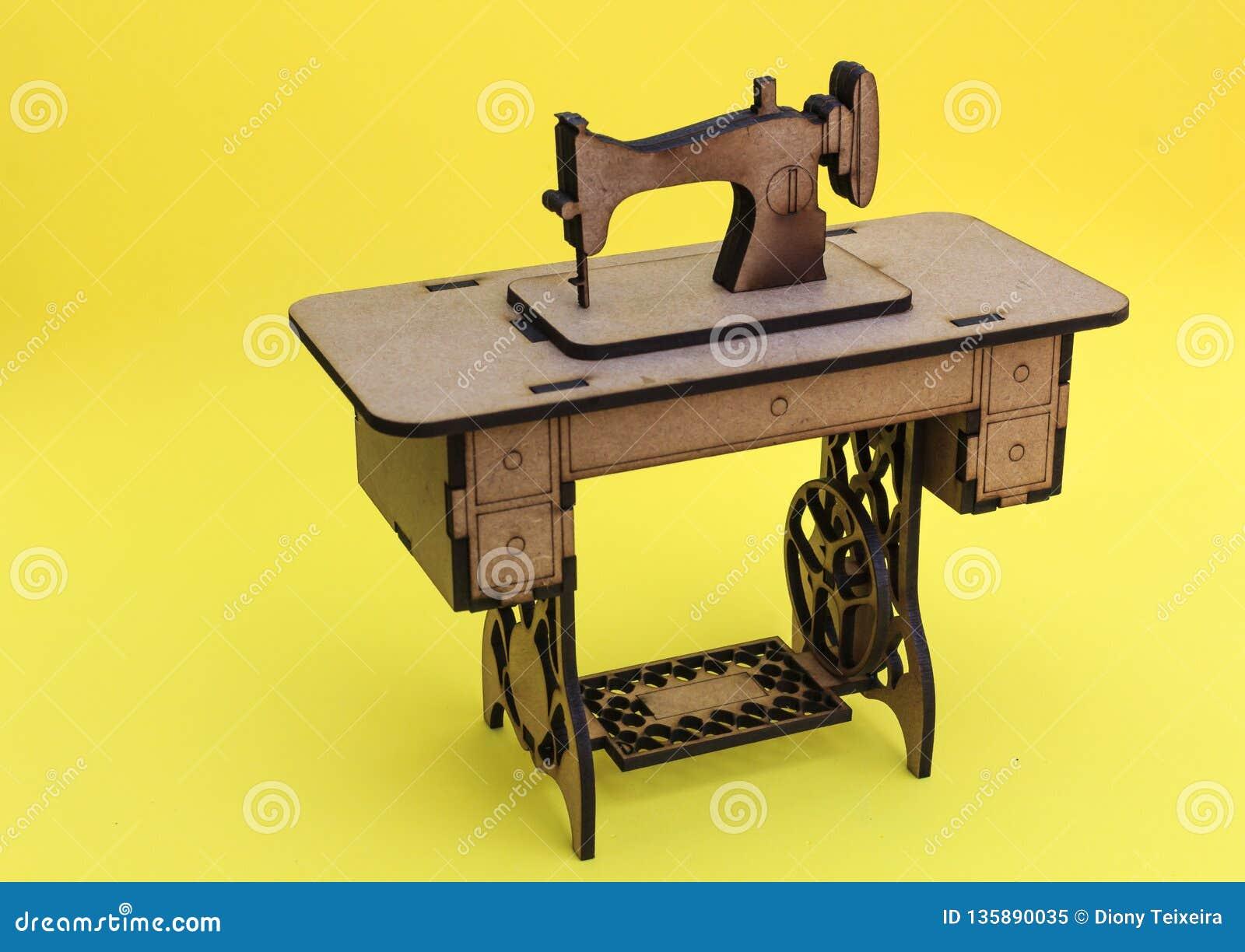 Mininähmaschine, hergestellt vom Holz, auf gelbem Hintergrund