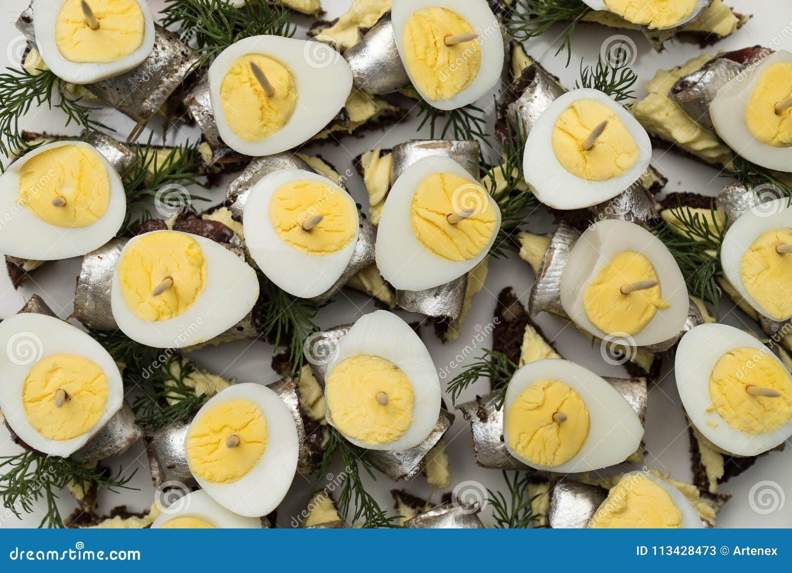 Minisandwich met zoute sprot en gesneden gekookt kwartelsei op de boterham De ingeblikte vis is Estlands nationaal voedsel Concep