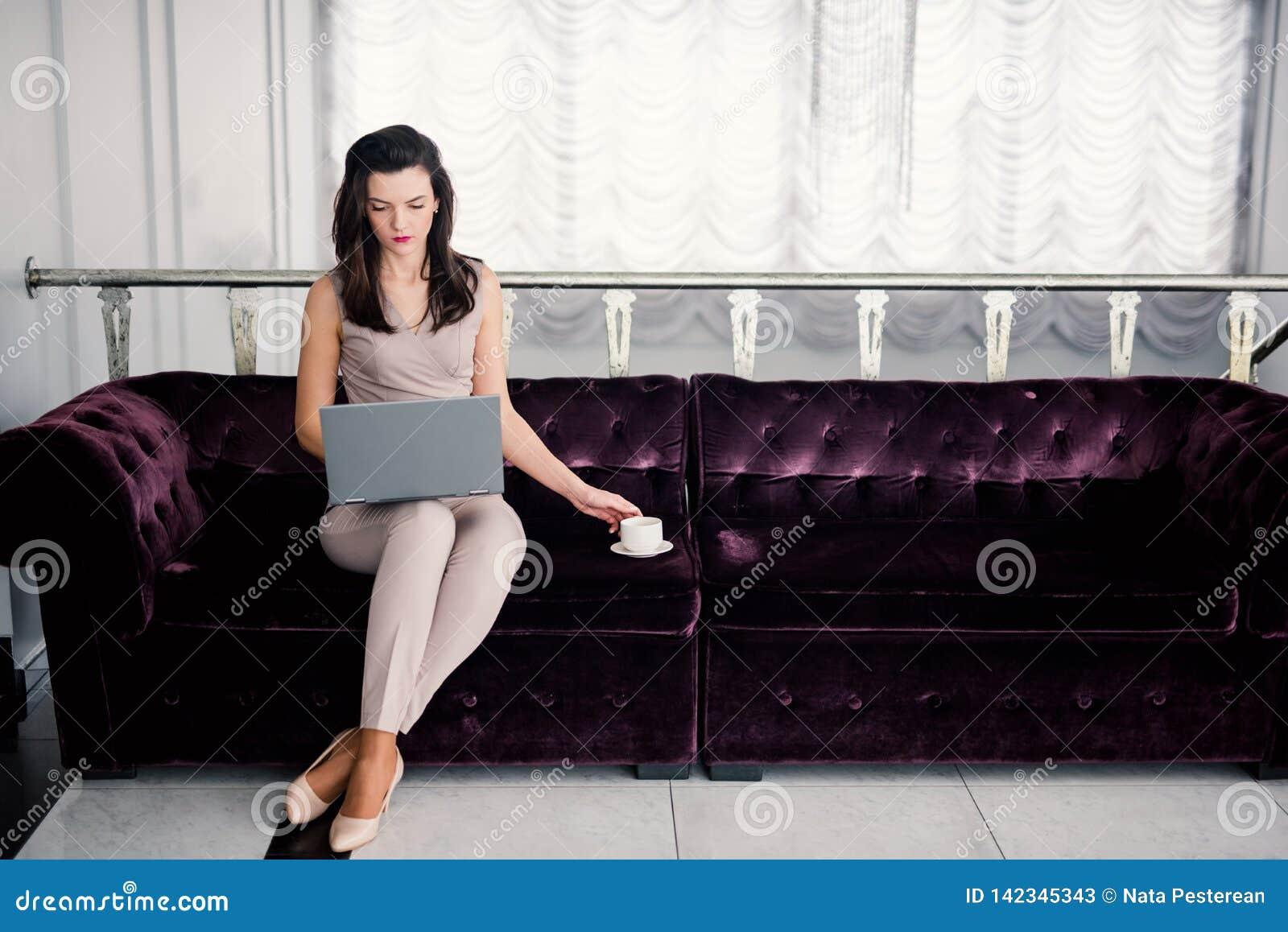 Ministerstwo Spraw Wewn?trznych Pomy?lny m?ody pi?kny kobiety obsiadanie na kanapie w ?ywym pokoju i u?ywa? laptopie, trzyma coff