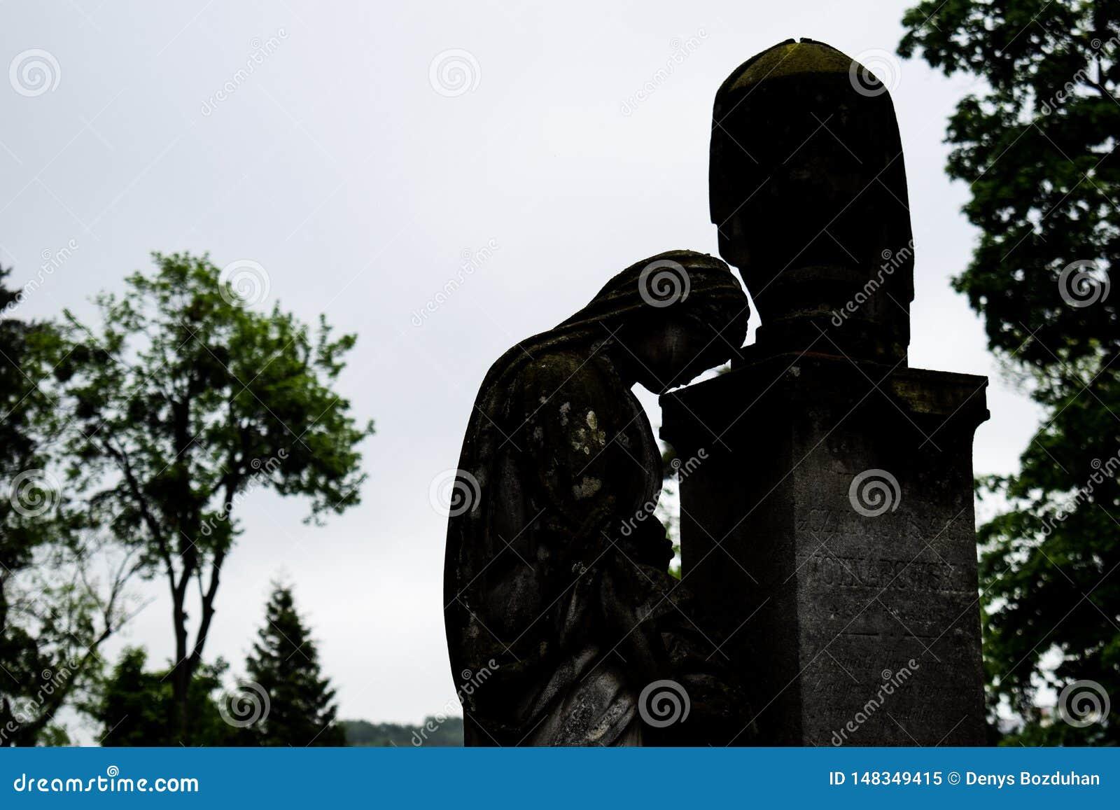 Minnes- staty för gammal gravsten i forntida kyrkogård härlig ledsen staty av flickan i gammal kyrkogård av Lviv