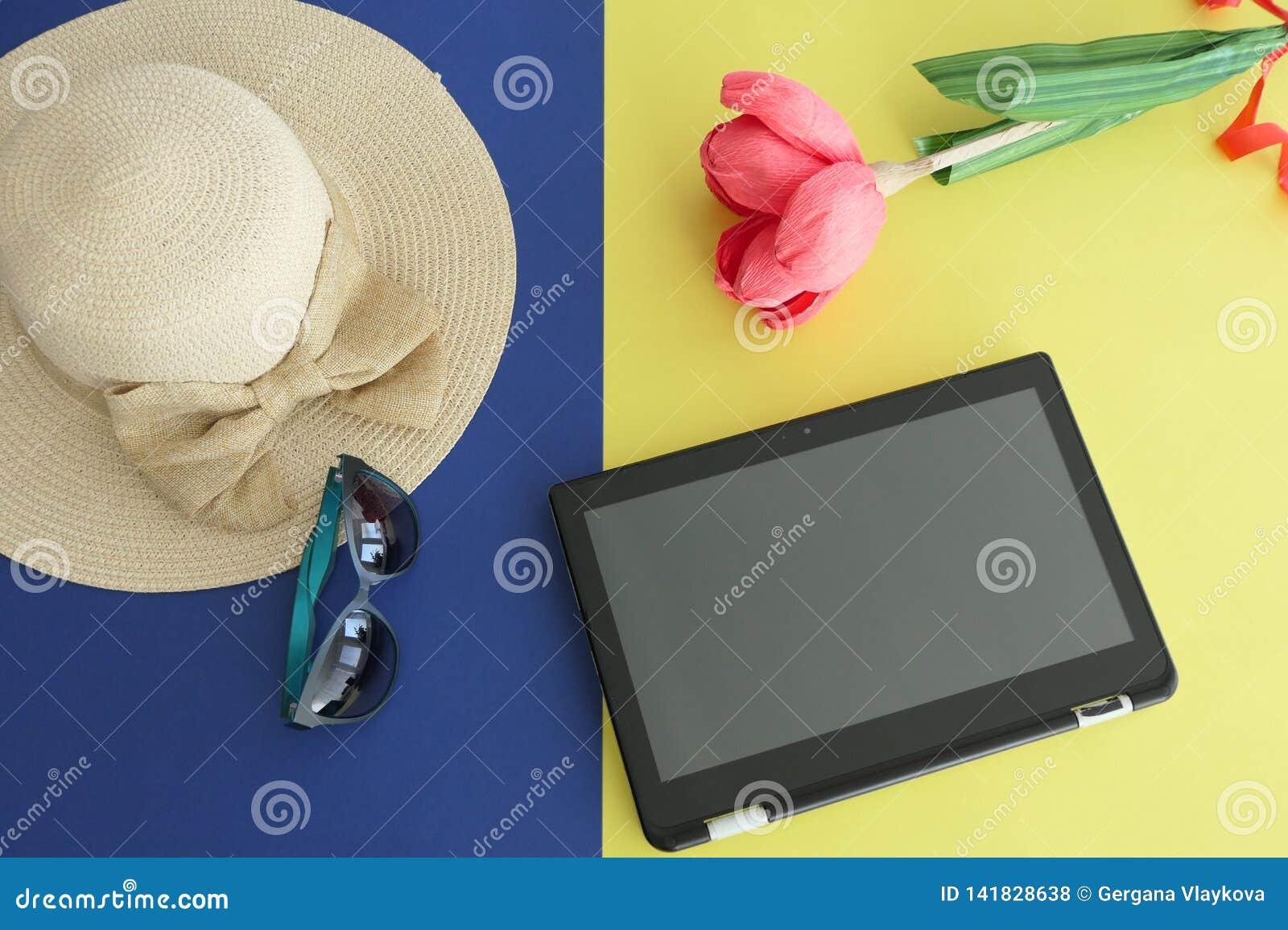 Minnestavla Straw Beach Female Hat med en pilbåge, solglasögon och en pappers- handgjord blomma som isoleras på gul och blå bakgr