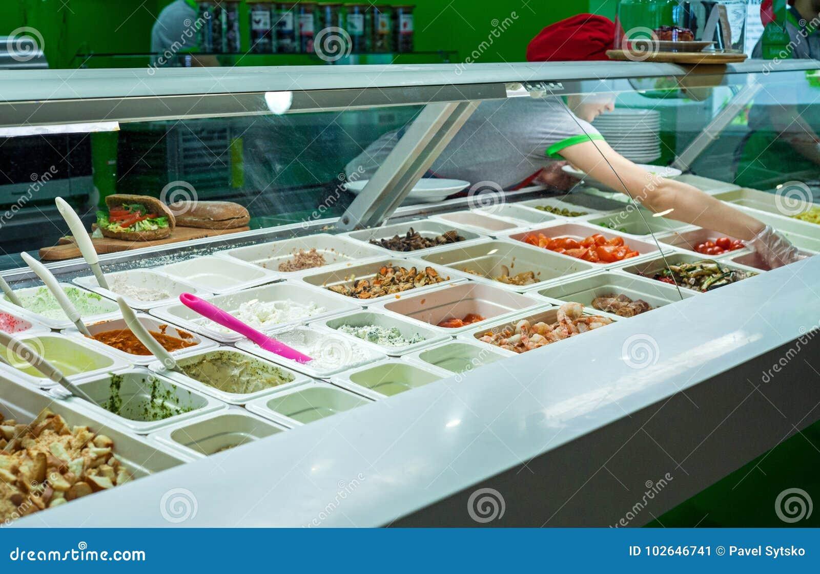 Minsk, Belarus - iune 17, 2017 : Un cuisinier prépare un plat avec assorti des ingrédients dans un ` de Salateira de ` de restaur