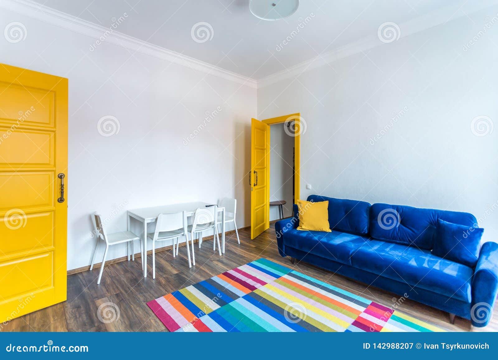 MINSK, BELARUS - mars 2019 : rétro intérieur lumineux des appartements plats de hippie avec le sofa bleu, la porte jaune et le ta