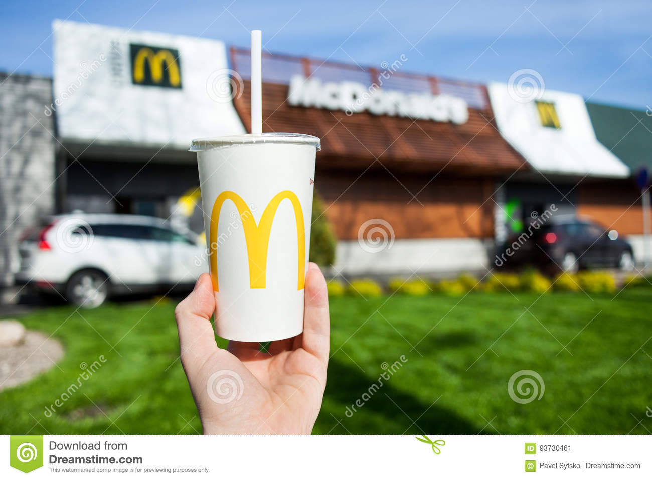 Minsk, Belarus, may 18, 2017: McDonald's soft drink paper cup in hand on blurry McDonald's Restaurant background