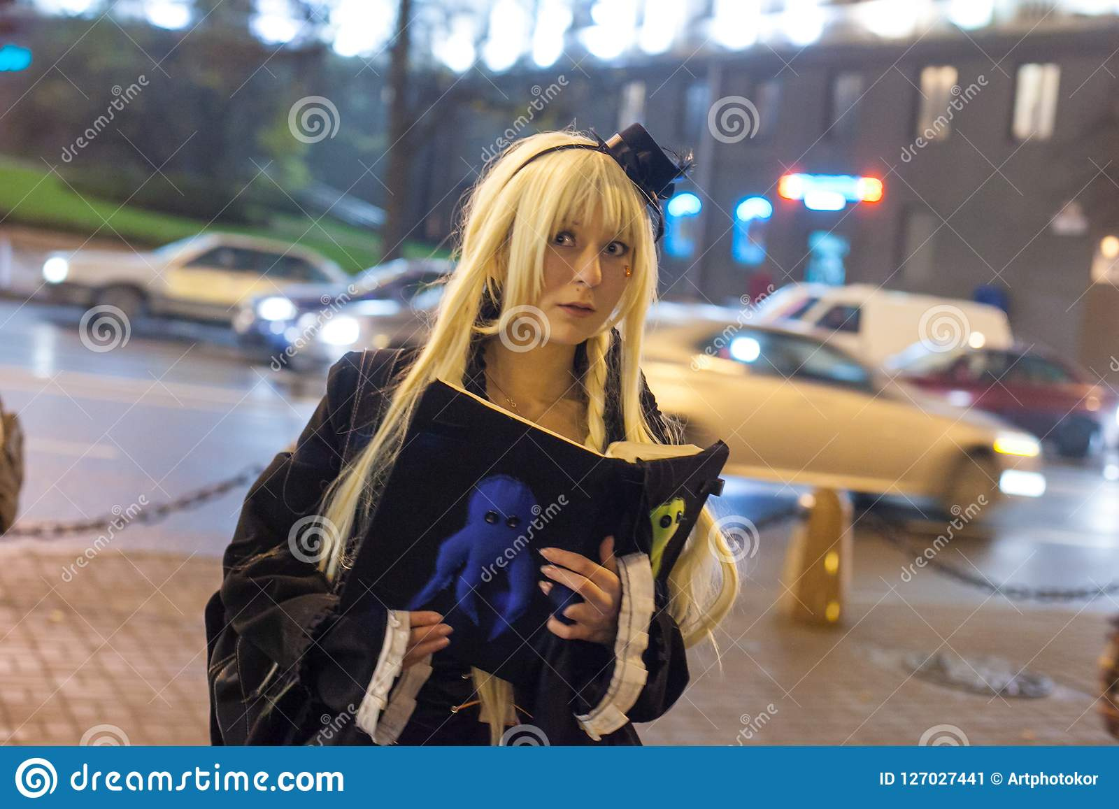 Young lady dressed in black costume, having book in hands