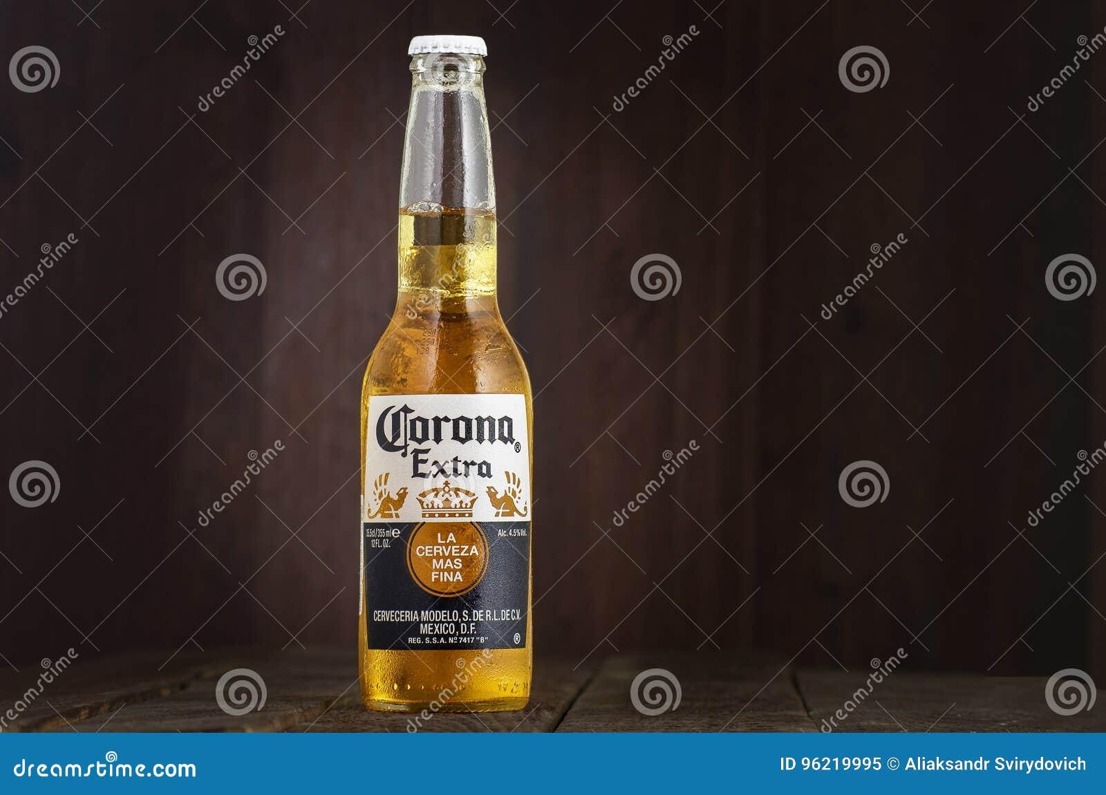 MINSK VITRYSSLAND - JULI 10, 2017: Redaktörs- foto av flaskan av Corona Extra öl på wood bakgrund, en av överkanten