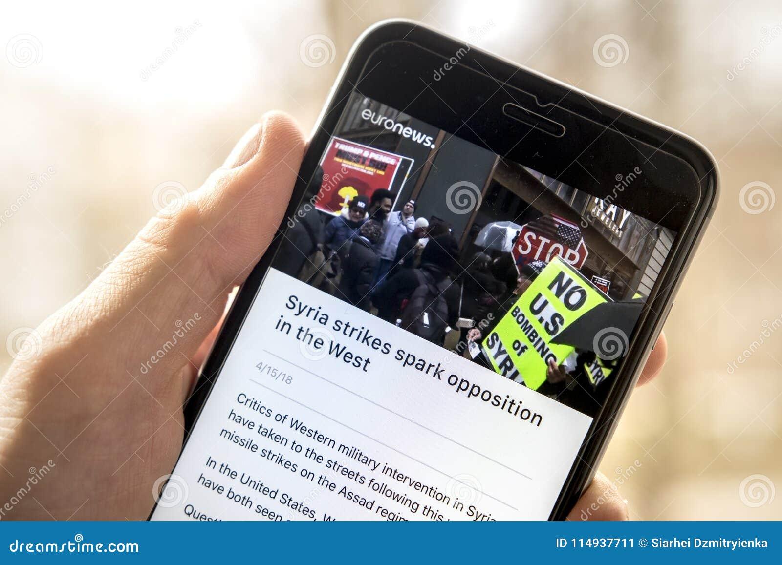 Minsk, Wit-Rusland - April 14, 2018: Het artikel over stakingen in Syrië op het scherm van moderne smartphone in euronews kanalis