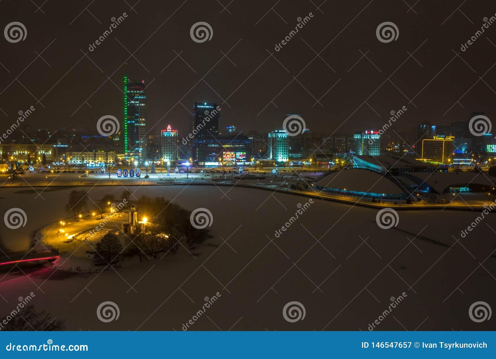 MINSK, WIT-RUSLAND - DECEMBER 2018: lichten van de nachtstad Lichte wolkenkrabber in de winterlandschap