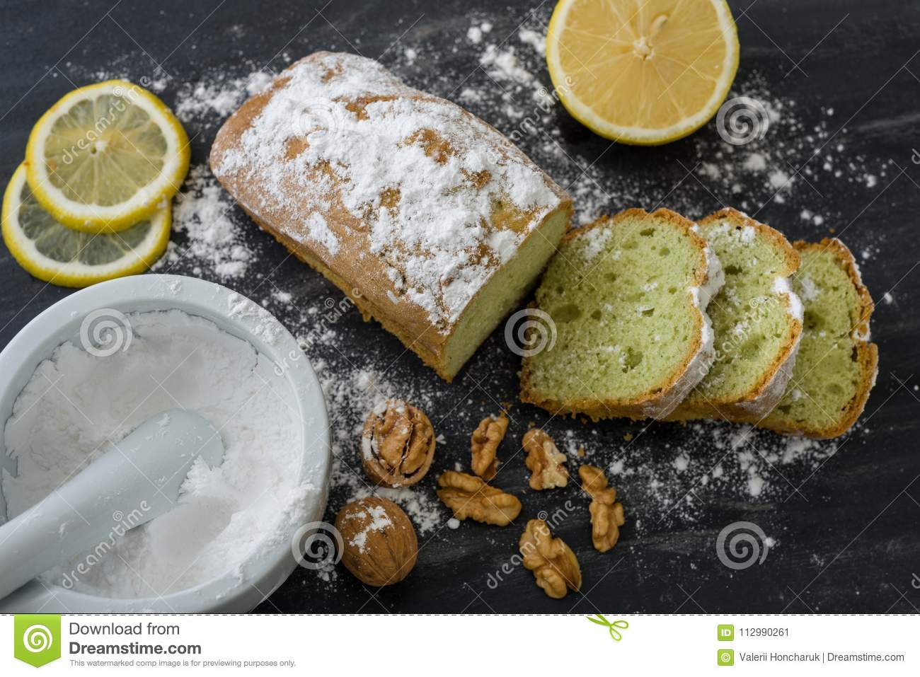 Mint cake on black surface with lemon, nuts, powdered sugar