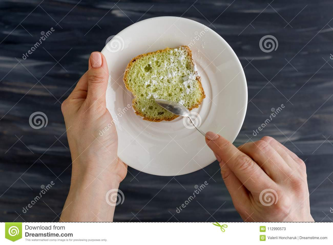 Mint cake on plate in hands, background dark surface