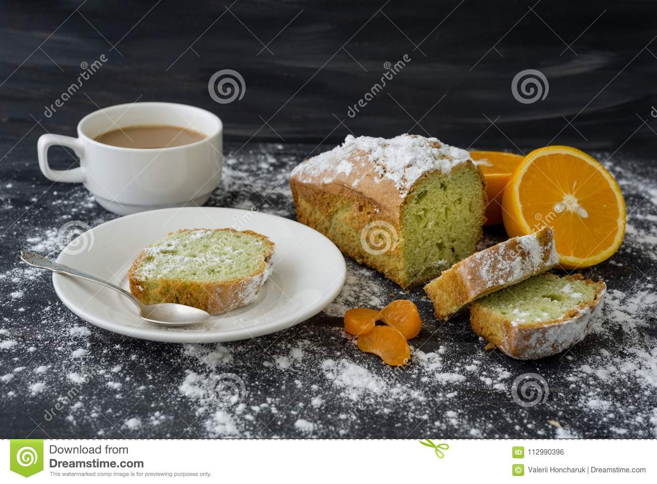 Mint cake sprinkled with powdered sugar on dark surface with fresh oranges mandarins