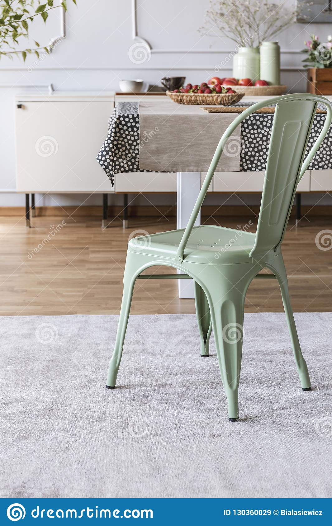 Mint Green Chair On Grey Carpet At Table In Rustic Dining Room Interior With Lamp And