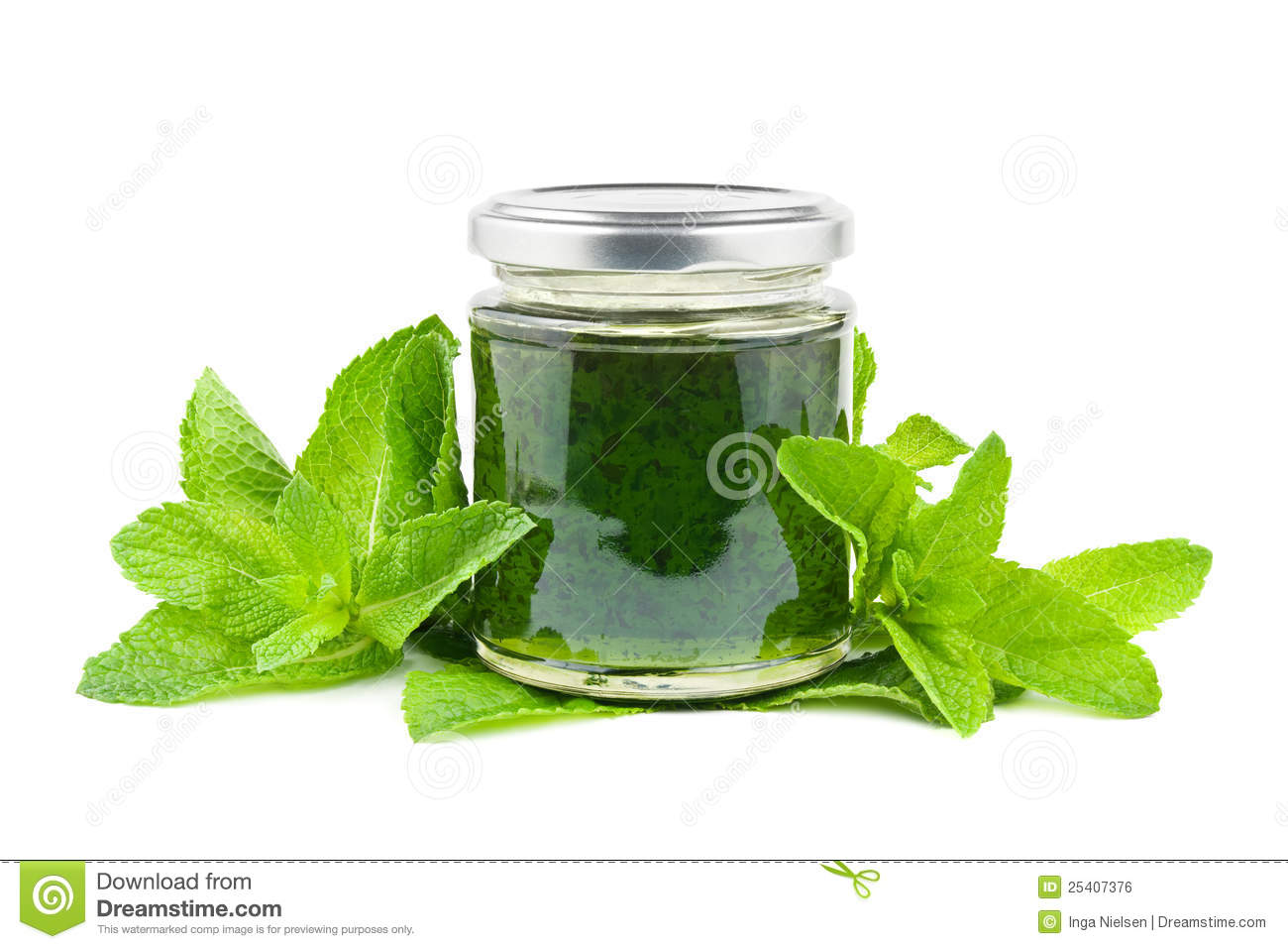 Jar with mint jelly and mint leaves on white.