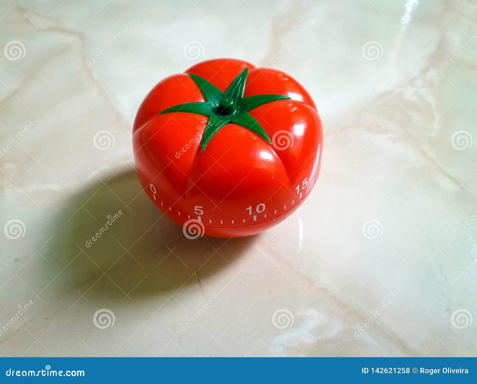 Minuterie rouge de pomodoro dans la forme de tomate sur un fond noir de texture