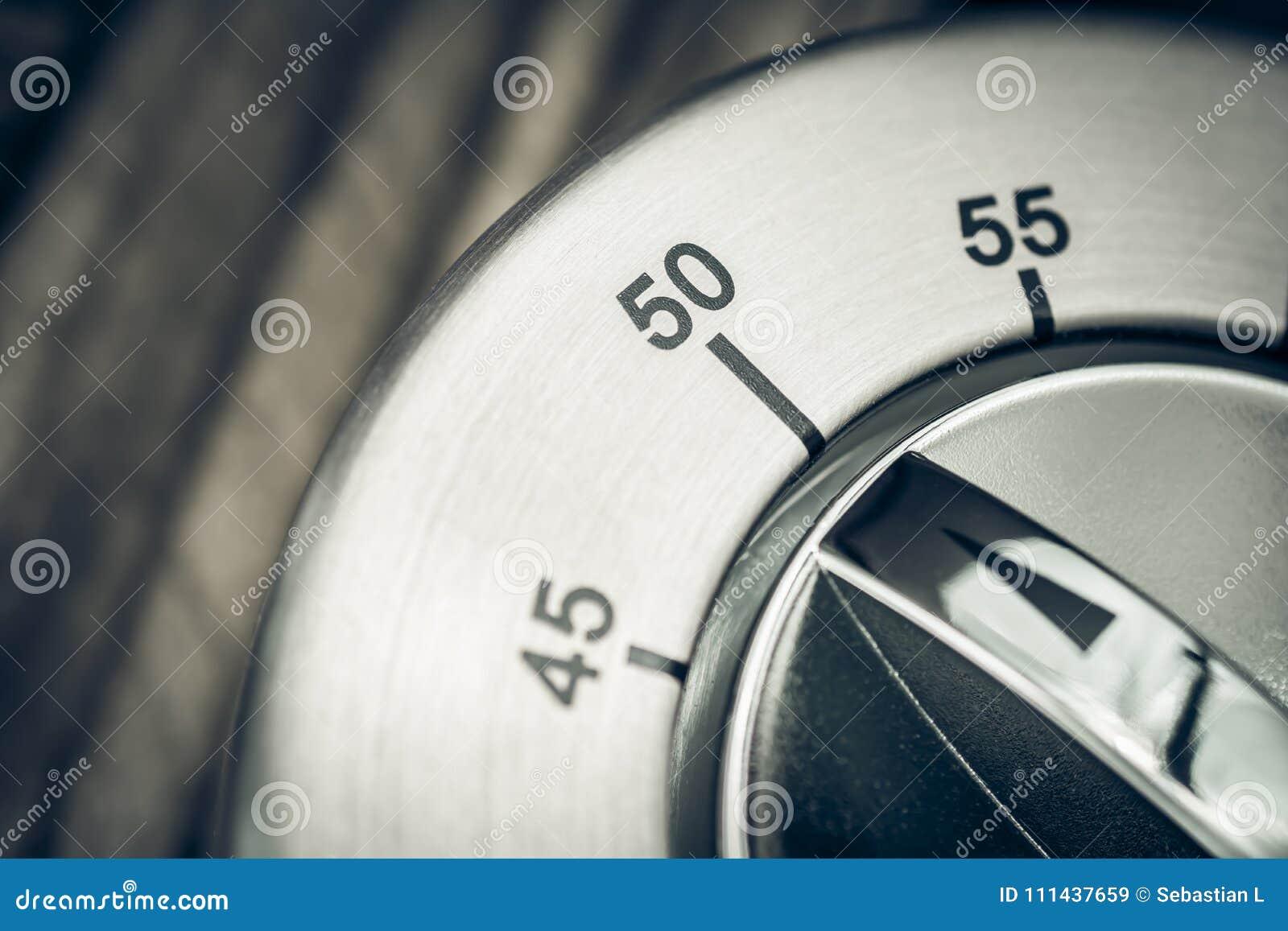 50 minutos - macro de um temporizador análogo da cozinha de Chrome em T de madeira