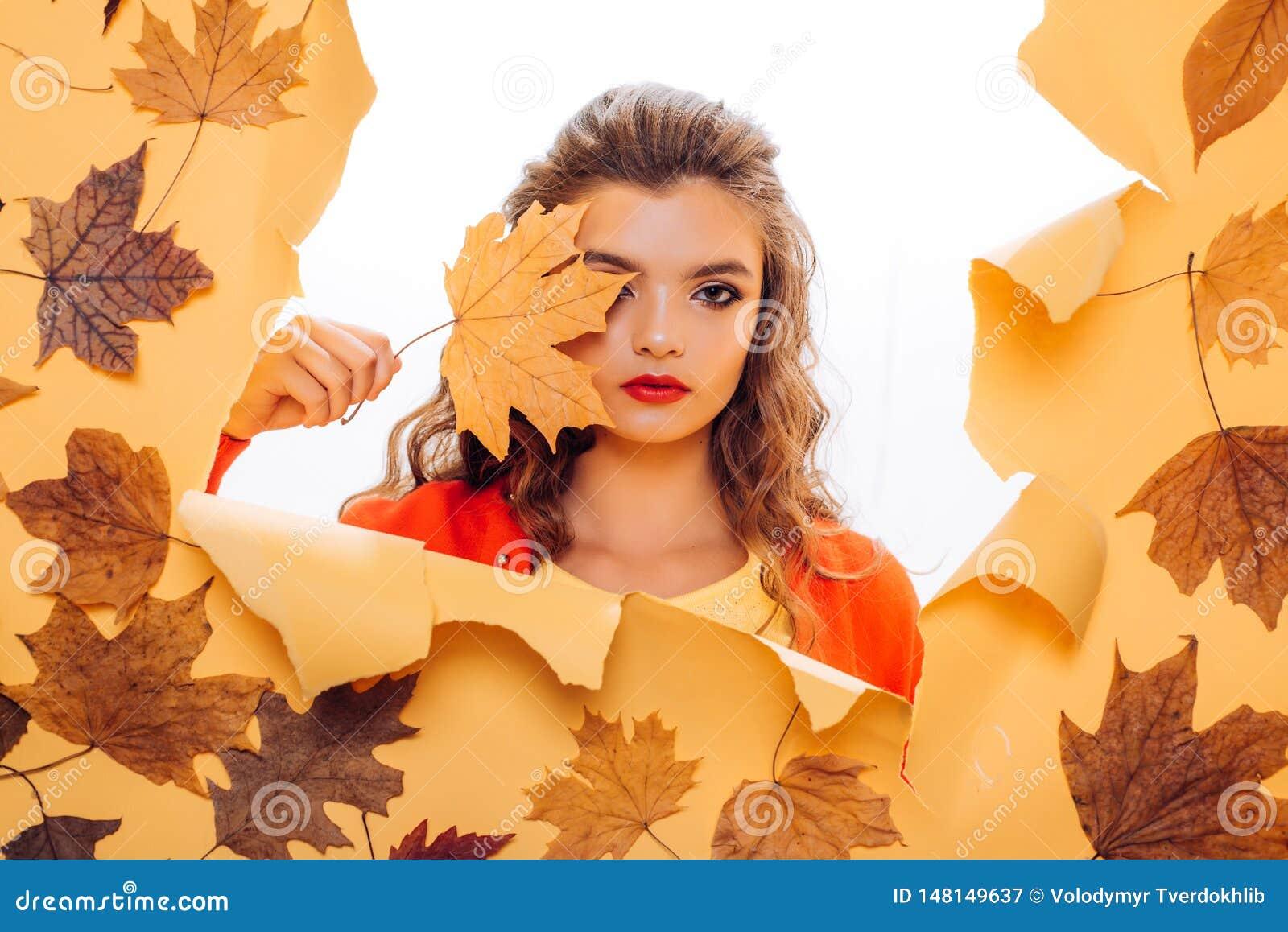 Mirada de la caída Ojeada de la muchacha de maquillaje a través del papel rasgado Cara bonita de la cubierta de la muchacha con l