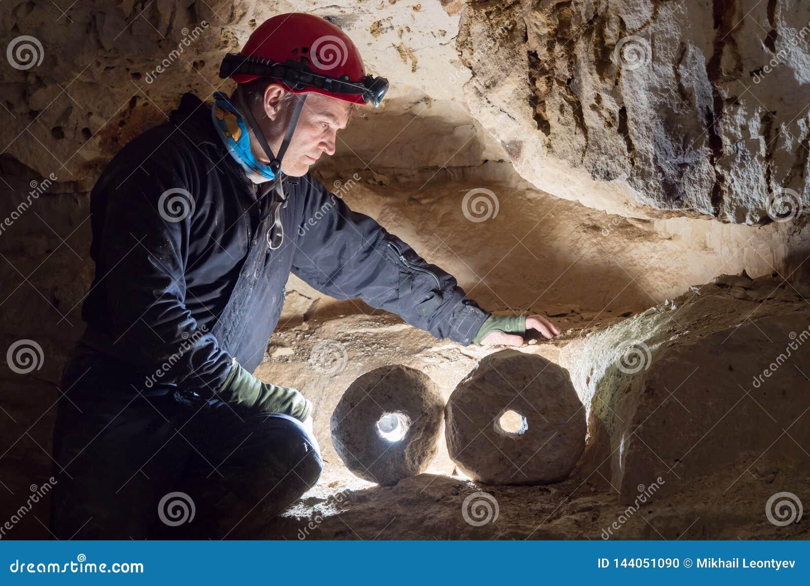 Mirada del arqueólogo en la rueda de piedra iluminada por el contraluz en las cuevas
