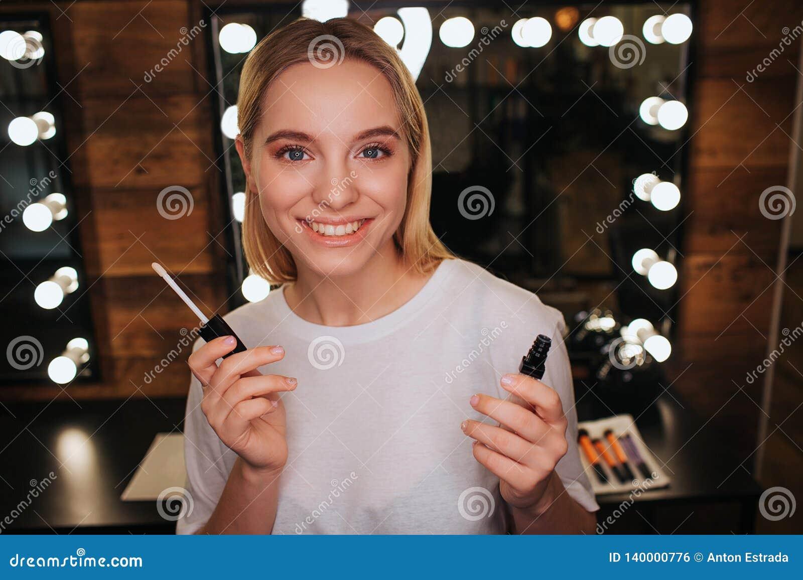 Mirada positiva alegre de la mujer joven en cámara y sonrisa Ella lleva a cabo lipgloss y actitud Espejo con las bombillas detrás