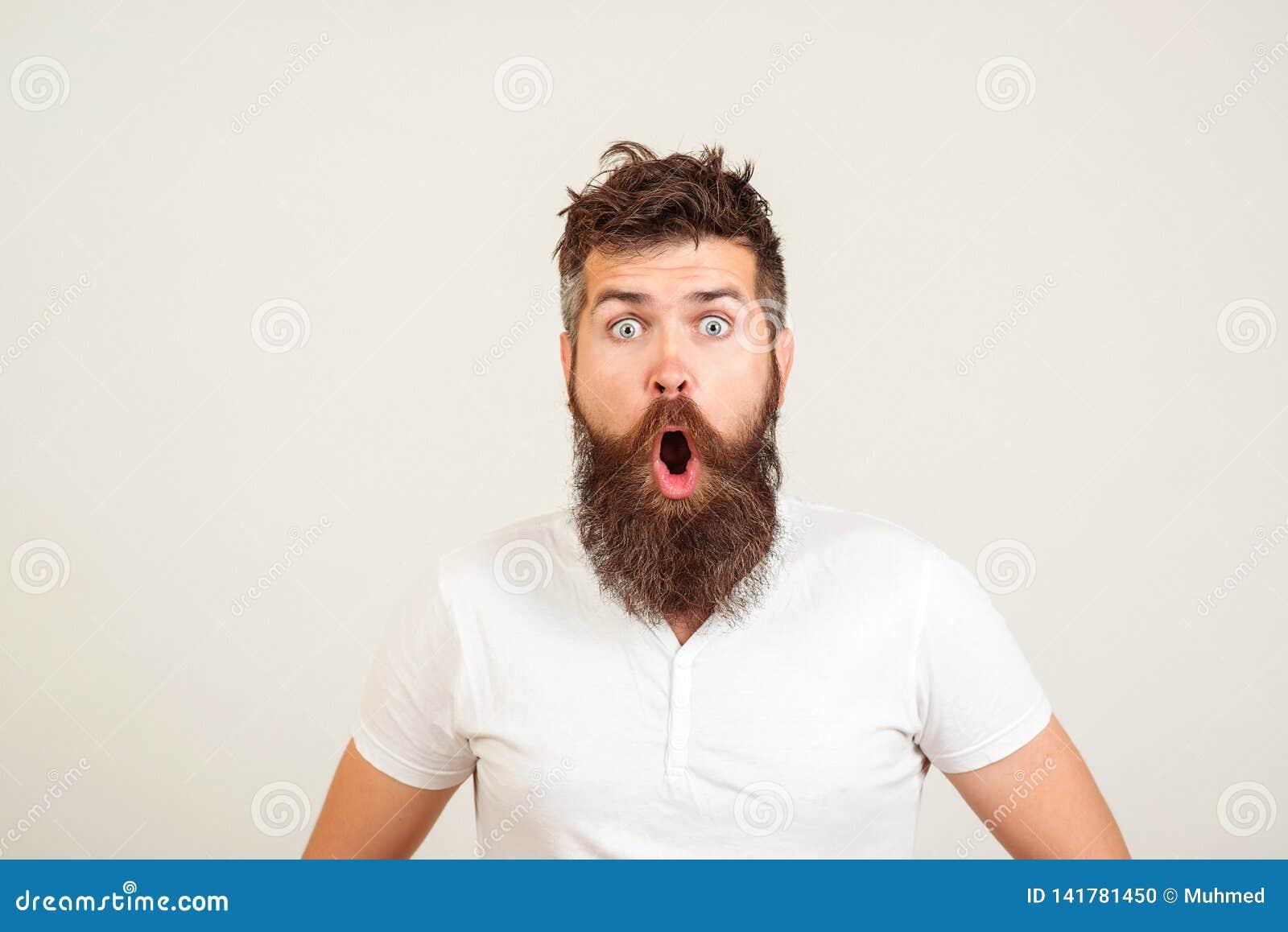 Miradas fijas barbudas chocadas del hombre en la cámara El individuo barbudo del inconformista abrió extensamente la boca y ojos