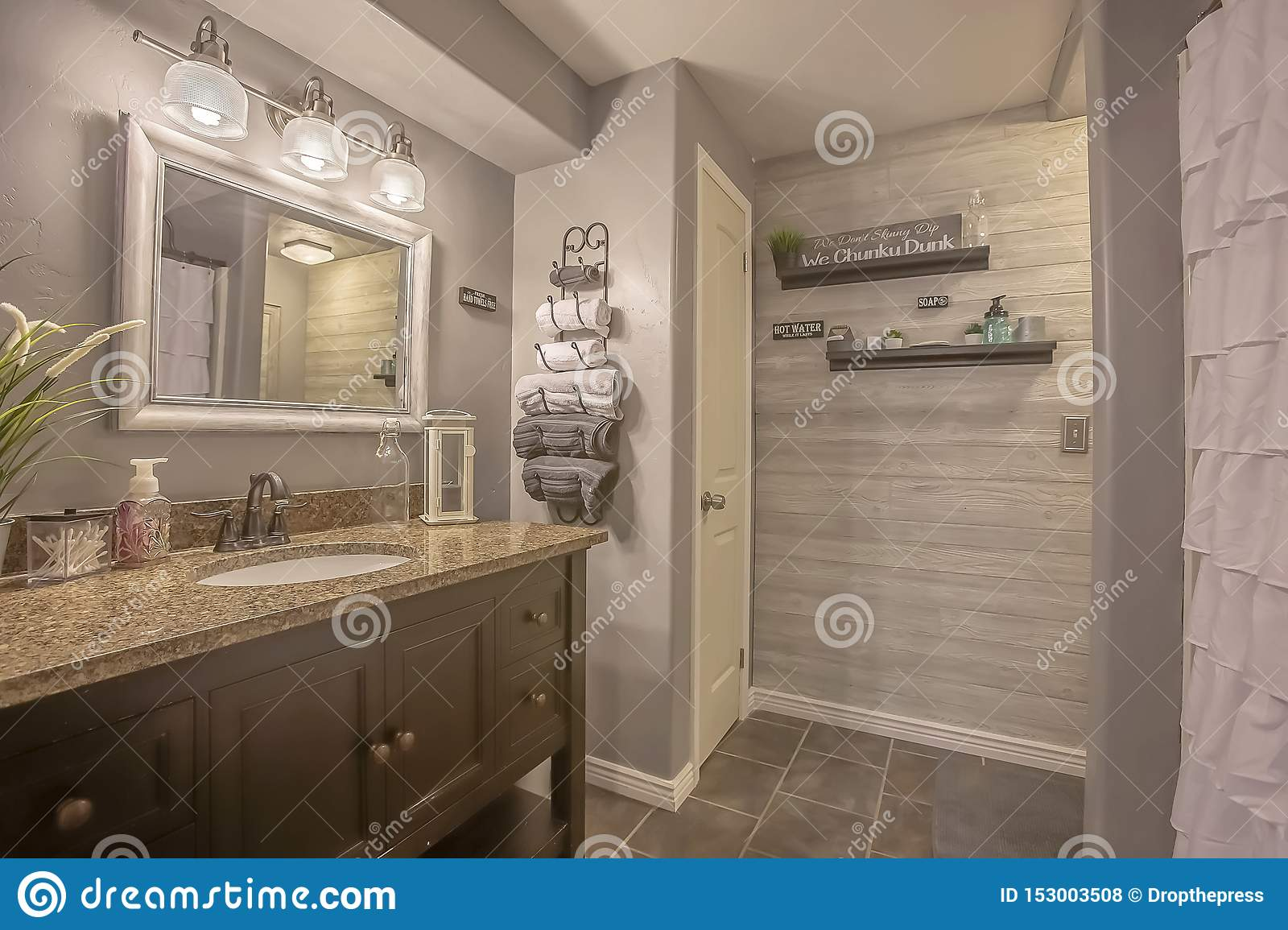 Mirror And Lamps Above The Vanity Inside A Bathroom With